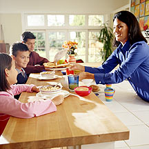 Woman feeding two kids breakfast